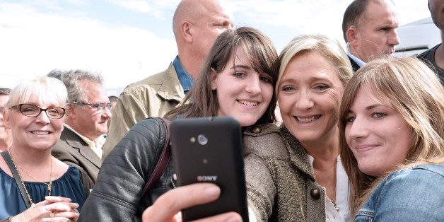French far-right National Front (Front National, FN) party President Marine Le Pen, poses in a selfie photographs with young people as she arrives at the 28th International Livestock Trade Fair (SPACE, Salon international des Productions Animales) outside Rennes, northwestern France, on September 17, 2015. AFP PHOTO / JEAN FRANCOIS MONIER        (Photo credit should read JEAN-FRANCOIS MONIER/AFP/Getty Images)