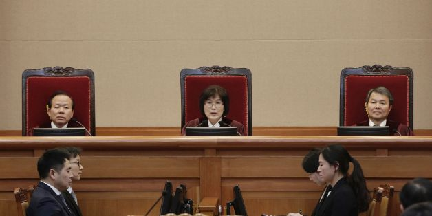 South Korean acting Constitutional Court's Chief Judge Lee Jung-mi, center, attends the final hearing on whether to confirm the impeachment of President Park Geun-hye, at the Court in Seoul February 27, 2017. Special prosecutors investigating the swirling corruption scandal that has embroiled South Korea's impeached President Park Geun-Hye and a host of major companies lost a bid to extend their inquiry on February 27. / AFP / POOL / Ahn Young-joon        (Photo credit should read AHN YOUNG-JOON