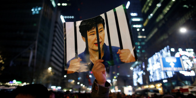 A man holds up a picture bearing an image of South Korean President Park Geun-hye as he attends a ceremony to celebrate the new year after a protest demanding Park's resignation, in Seoul, South Korea, December 31, 2016.   REUTERS/Kim Hong-Ji