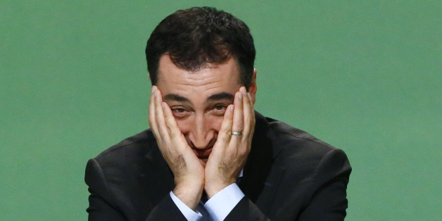 Cem Oezdemir of the environmental Greens party (Die Gruenen) holds his head in his hands during party meeting in Berlin October 19, 2013. REUTERS/Tobias Schwarz (GERMANY - Tags: POLITICS)
