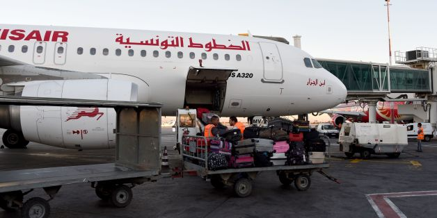 A picture taken on July 19, 2016 at Tunis-Carthage International Airport shows a labourer transporting luggage next to a Tunisair plane. / AFP PHOTO / FETHI BELAID        (Photo credit should read FETHI BELAID/AFP/Getty Images)