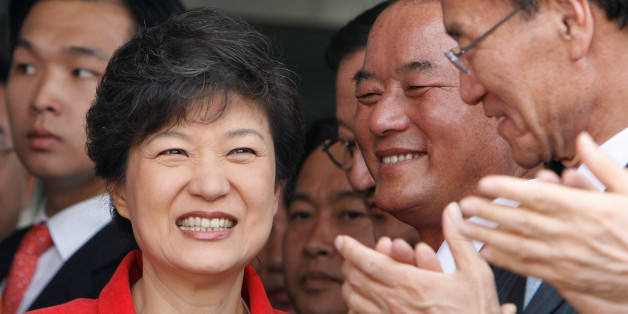 FILE PHOTO: Lawmakers and supporters of Park Geun-hye (L) clap their hands at the main office of the main opposition Grand National Party (GNP) in Seoul June 11, 2007.   REUTERS/Lee Jae-Won/File Photo