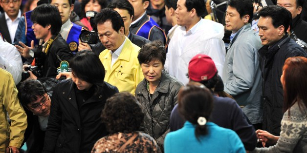 South Korea's President Park Geun-Hye (C) visits relatives of missing passengers on board a capsized ferry as they wait for news at a gym in Jindo on April 17, 2014. Rescuers worked frantically on April 17 to find 300 people -- mostly schoolchildren -- missing after a South Korean ferry capsized, with prospects of pulling survivors from the submerged vessel dimming as emotions boiled over among anguished relatives.       AFP PHOTO / JUNG YEON-JE        (Photo credit should read JUNG YEON-JE/AFP/