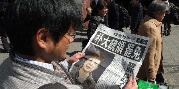 A man reads an extra edition of a Japanese major newspaper reporting on South Korean President Park Geun-hye's impeachment in Tokyo on March 10, 2017.  South Korean President Park Geun-Hye was fired by the country's top court on March 10, as it upheld her impeachment by parliament over a wide-ranging corruption scandal. / AFP PHOTO / Kazuhiro NOGI        (Photo credit should read KAZUHIRO NOGI/AFP/Getty Images)