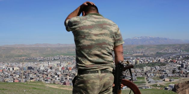 TOPSHOT - A Turkish soldier gestures while standing on the hill overlooking damaged buildings following heavy fighting between government troops and Kurdish fighters in the Kurdish town of Cizre in southeastern Turkey, which lies near the border with Syria and Iraq, on March 2, 2016.  Thousands in Turkey's Kurdish-majority town of Cizre started returning to their homes on March 2 after authorities partially lifted a curfew in place since December for a controversial military operation to root out separatist rebels.  / AFP / YASIN AKGUL        (Photo credit should read YASIN AKGUL/AFP/Getty Images)