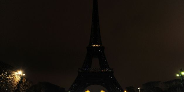 A person dressed as a WWF panda stands near the Eiffel Tower in Paris after it went dark for the Earth Hour environmental campaign on March 19, 2016. / AFP / THOMAS OLIVA        (Photo credit should read THOMAS OLIVA/AFP/Getty Images)