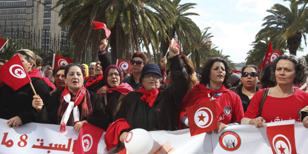 Tunisian women wave flags during a march to celebrate International Women's Day in Tunis March 8, 2014. On March 8 activists around the globe celebrate International Women's Day, which dates back to the beginning of the 20th Century and has been observed by the United Nations since 1975. The UN writes that it is an occasion to commemorate achievements in women's rights and to call for further change.  REUTERS/Zoubeir Souissi (TUNISIA - Tags: SOCIETY)