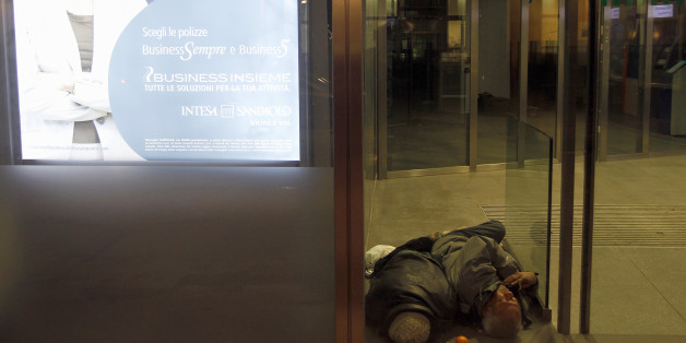 A homeless man sleeps inside the withdrawal area of a bank in downtown Milan February 9, 2012. Sub-freezing winter weather temperatures continued to hit Europe.  REUTERS/Stefano Rellandini (ITALY - Tags: ENVIRONMENT SOCIETY POVERTY)