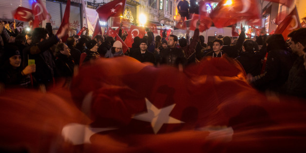 ISTANBUL, TURKEY - MARCH 12:  Protesters hold a large Turkish flag as they sing songs and chant slogans  outside the Dutch Consulate on March 12, 2017 in Istanbul, Turkey.  Protesters gathered outside the consulate after the Turkish foreign minister, who was scheduled to speak in the Dutch city of Rotterdam, was refused entry and his plane banned from landing. In response to the action Turkish President Recep Tayyip Erdogan speaking at a referendum rally described the Dutch as ' Nazi remnants and fascists'  (Photo by Chris McGrath/Getty Images)