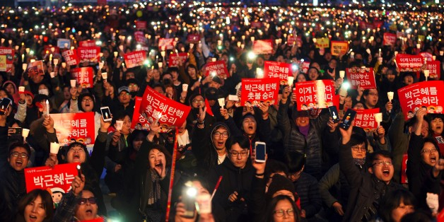 South Korean demonstrators hold up candles during a candlelit rally demanding arrest of Park Geun-Hye in Seoul on March 11, 2017.