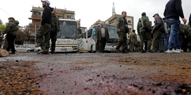 Syrian security forces and locals gather at the scene of a bombing following twin attacks targeting Shiite pilgrims in Damascus' Old City on March 11, 2017, in one of the bloodiest attacks in the Syrian capital.A roadside bomb detonated as a bus passed and a suicide bomber blew himself up in the Bab al-Saghir area, which houses several Shiite mausoleums that draw pilgrims from around the world, the Syrian Observatory for Human Rights said. / AFP PHOTO / Louai Beshara        (Photo credit should
