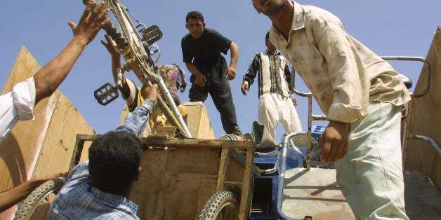 A group of 450 Iraqi refugees arrive in the southern Iraqi port city of Basra 23 September 2003 from Saudi Arabia, after spending 12 years in a desert camp in Rafha. The group had left for southern Iraq via Kuwait in a convoy of nine buses and nine trucks carrying their belongings yesterday. According to the UN refugee agency UNHCR, the group was the fourth to return home from Saudi Arabia. AFP/PHOTO/Ahmad Al-Rubaye  (Photo credit should read AHMAD AL-RUBAYE/AFP/Getty Images)