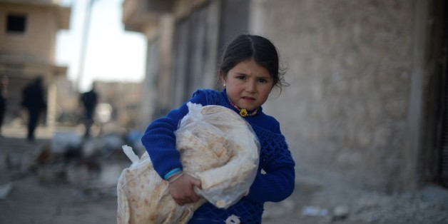 ALEPPO, SYRIA - MARCH 07: A Syrian girl carries a pile of bread, provided by the Foundation for Human Rights and Freedoms and Humanitarian Relief (IHH), a Turkish NGO in Al-Bab town of Aleppo, Syria on March 07, 2017. Syrians who have returned to their home after the Al Bab town center has been entirely freed from Daesh terrorists as part of the 'Operation Euphrates Shield', prepare to start a new life in the area. The Turkish-led Operation Euphrates Shield began on August 24, 2016 to improve security, support coalition forces and eliminate the terror threat along the Turkish border using Free Syrian Army fighters backed by Turkish artillery and jets. (Photo by Huseyin Nasir/Anadolu Agency/Getty Images)