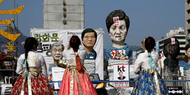 Tourists wearing traditional costume 'Hanbok' take picture of a statue depicting South Korea's ousted leader Park Geun-hye in Seoul, South Korea, March 13, 2017. REUTERS/Kim Kyung-Hoon