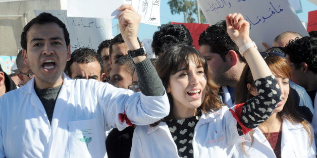 Tunisian doctors shoot anti-government slogans during a demonstration against a draft bill that aims at forcing them to work in rural areas on January 7, 2014 outside the headquarters of the National Constituent Assembly where debates take place on Tunisia's new constitution. (L) the placard reads words by late Nelson Mandela 'A decision taken without us but about us is a decision taken against us'. AFP PHOTO / FETHI BELAID        (Photo credit should read FETHI BELAID/AFP/Getty Images)