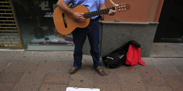 "Unemployed Paco, 51, plays his guitar as he ask for alms in the Andalusian capital of Seville, southern Spain June 17, 2013. Spain's economy may show a clear turnaround in the second quarter according to available economic data, Treasury Minister Cristobal Montoro said on Monday during a conference in the northern city of Santander. The placard reads, ""My last round, thanks Rajoy"".  REUTERS/Marcelo del Pozo (SPAIN - Tags: SOCIETY BUSINESS)"