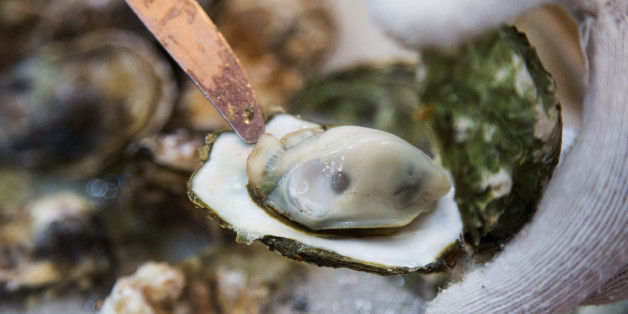 A diner picks up an oyster at a restaurant in Tongyeong, South Korea, on Sunday, Dec. 27, 2015. South Korea's biggest brokerage predicts the won is headed for its steepest annual slide in eight years as the government favors depreciation to revive exports and stave off deflation. Photographer: SeongJoon Cho/Bloomberg via Getty Images