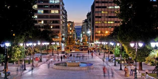 Athens, Greece- October 1, 2007: Night view of the the Syntagma square in the capital city of Greece in Athens with people and tourists walking around.