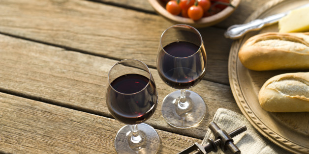 Red wine on a rustic picnic table.More rustic outdoor wine shots: