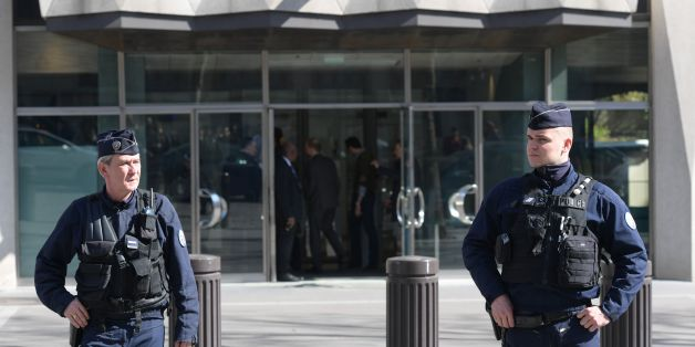 TOPSHOT - Members of the POlice Forensic team leave the Paris offices of the International Monetary Fund (IMF) on March 16, 2017 in Paris, after a letter bomb exploded in the premises.An employee at the Paris offices of the International Monetary Fund suffered injuries to her hands and face after opening a letter which exploded on March 16, police said. Several people were evacuated from the building near the Arc de Triomphe monument 'as a precaution', a police source said. / AFP PHOTO / Christo