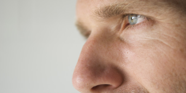 Close-up shot of a man's blue eye and prominent nose