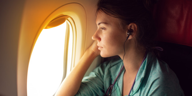 Young woman sitting in the plane, looking away through the window and listeting music with headphones