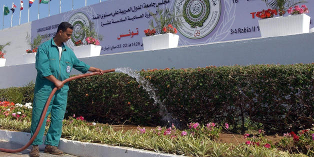 TUNIS, TUNISIA:  A municipal employee waters 19 May 2004 the flowers in front of the Congress Palace of Tunis, three days before the beginning of the Arab League Summit 16th ordinary session.  AFP PHOTO/FETHI BELAID  (Photo credit should read FETHI BELAID/AFP/Getty Images)
