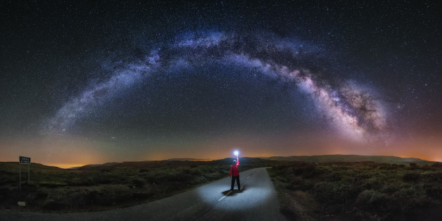 A young man on a road watching the Milky Way and lightning the road with a flash. Taken in A Veiga, Orense.