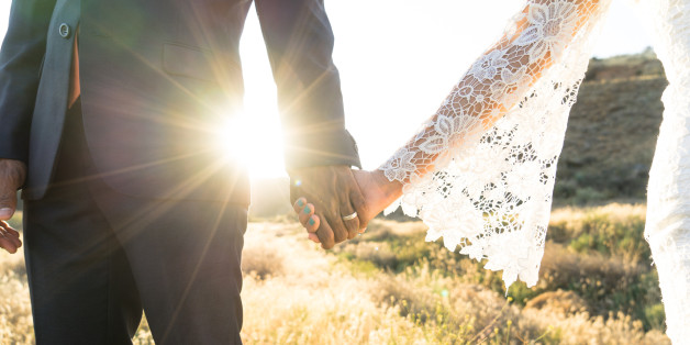 An Interracial couple holding hands backlit by the flaring sun