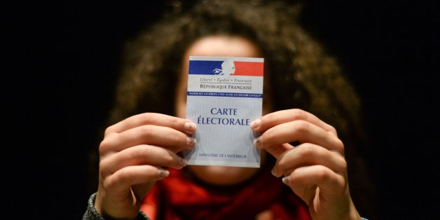 A woman holds her first electoral card, on March 19, 2017, in Besancon, eastern France.  / AFP PHOTO / Sébastien BOZON        (Photo credit should read SEBASTIEN BOZON/AFP/Getty Images)