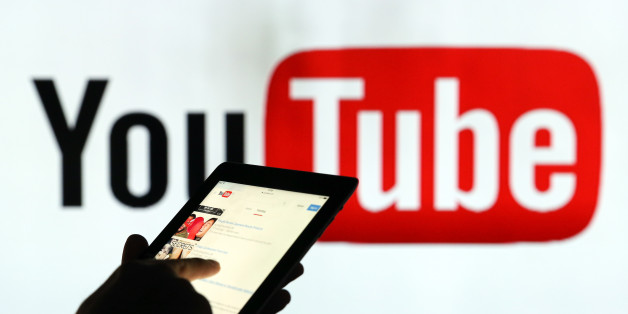 A man is seen as a silhouette as he checks a mobile device whilst standing against an illuminated wall bearing YouTube Inc.s logo in this arranged photograph in London, U.K., on Tuesday, Jan. 5, 2016. YouTube Inc. provides consumer media and entertainment through its website. Photographer: Chris Ratcliffe/Bloomberg via Getty Images