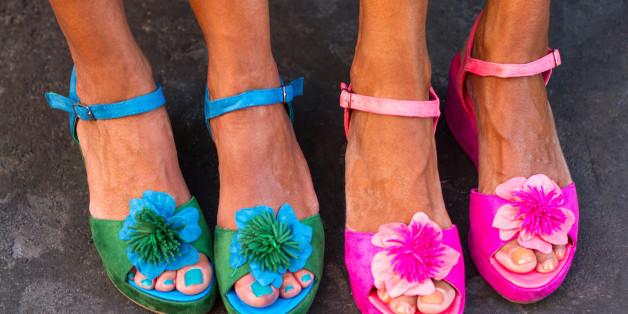 Four pretty pedicured feet in flowery sandals, side-by-side.