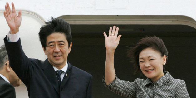 Japan's Prime Minister Shinzo Abe (L) and his wife Akie wave before boarding an aircraft as they depart Tokyo's Haneda airport to attend the meeting of Asia-Pacific Economic Coorpoeration (APEC) leaders' summit in Sydney September 7, 2007. With its cabinet jolted by scandals and the opposition in control of parliament's upper house, Japan faces a policy vacuum that bodes ill for fixing creaking social welfare systems or loosening the government's grip on the economy. REUTERS/Kyodo (JAPAN) JAPAN