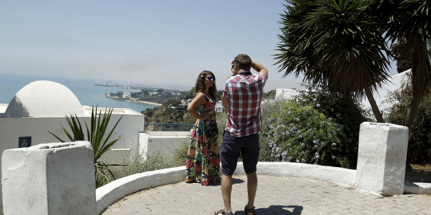 """A tourist takes pictures of his partner in Sidi Bou Said, a popular tourist destination near Tunis, Tunisia July 7, 2015. Tunisian President Beji Caid Essebsi declared a state of emergency on Saturday, saying the Islamist militant attack on a beach hotel that killed 38 foreigners had left the country """"in a state of war"""".   REUTERS/Zoubeir Souissi"""