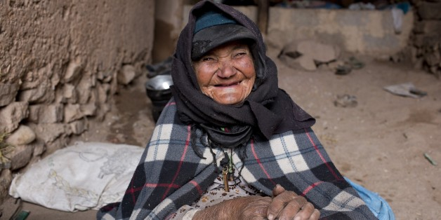 A woman smiles as she warms herself around a fire in her home in Tilmi village in the High Atlas region of Morocco February 13, 2015. The snowy foothills of the High Atlas mountains in Morocco are home to several Berber villages where the inhabitants make their living by farming, baking bread in traditional ovens, herding cattle, and the making and selling of honey, olive oil and pottery. Extreme weather fluctuations and erosion that causes flooding and landslides have led to a drop in agricultu