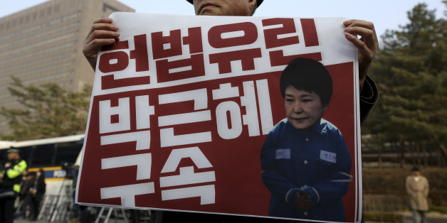 A protester demanding arrest warrant of ousted South Korean President Park Geun-hye holds a photograph of Park during a protest outside the prosecutor? office in Seoul, South Korea, on Tuesday, March 20, 2017. (Photo by STR/NurPhoto via Getty Images)