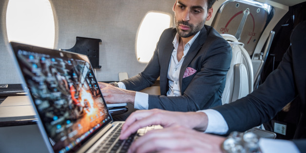Focus on well dressed businessmen in the back while looking at the screen of his colleague's laptop.