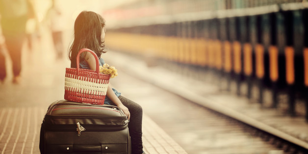 Little girl waiting in a railway station with bag and flower bouquet.