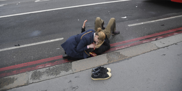A woman assist an injured person after an incident on Westminster Bridge in London, March 22, 2017.  REUTERS/Toby Melville