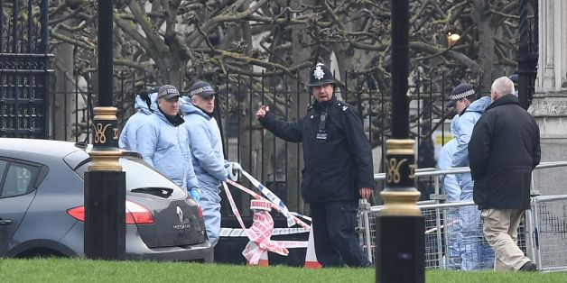 Police officers in forensics suits work at the scene on March 23, 2017 where the car collided with the gates of the Houses of Parliament during the March 22 terror attack in Westminster in central London. Britain's parliament reopened on Thursday with a minute's silence in a gesture of defiance a day after an attacker sowed terror in the heart of Westminster, killing three people before being shot dead. Sombre-looking lawmakers in a packed House of Commons chamber bowed their heads and police of