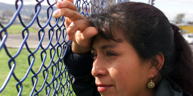 Ecuadorean Carmen Mainzanche bid farewell to her brother through the fence at the airport in Quito, April 30, 2003. Mainzanche is one of hundreds of Ecuadoreans gathered around at the airport every week to send off their relatives who leave the country. REUTERS/Guillermo Granja FOR FEATURE STORY ECUADOR EMIGRATION  GG/HK