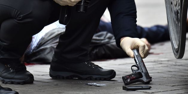 EDITORS NOTE: Graphic content / An Ukrainian police expert seizes a gun at the scene where former Russian MP Denis Voronenkov was shot dead on March 23, 2017 in the center of Kiev.Ukrainian President blamed Russia for the murder of Voronenkov, who moved to Ukraine last year and was wanted by Russia for fraud, saying it was an 'act of state terrorism.'  / AFP PHOTO / Sergei SUPINSKY        (Photo credit should read SERGEI SUPINSKY/AFP/Getty Images)