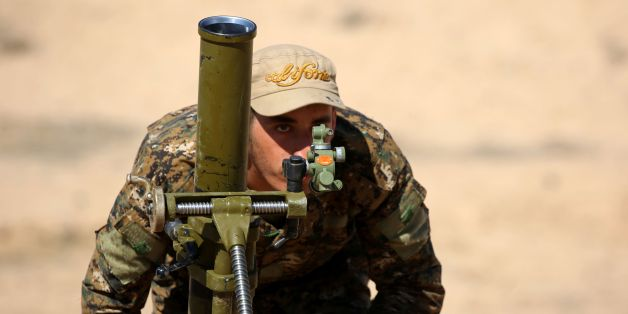 A fighter from the US-backed Syrian Democratic Forces (SDF), made up of an alliance of Arab and Kurdish fighters, prepares to fire a mortar launcher in the village of Sabah al-Khayr on the northern outskirts of Deir Ezzor as they drive to encircle the Islamic State (IS) group bastion of Raqa on February 21, 2017.The SDF made a major incursion into the oil-rich province of Deir Ezzor as part of their push for Raqa, field commander Dejwar Khabat said.  / AFP / DELIL SOULEIMAN        (Photo credit