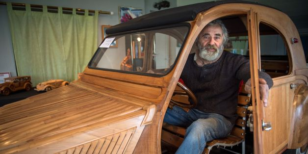 French cabinetmaker Michel Robillard poses in his handbuilt wooden 2CV Citroen Car built as an exact one/one replica on March 20, 2017, near Loches, Central France. A retired cabinetmaker has just completed the production of a Citroen 2 CV in a Touraine fruitwood, a life-size vehicle unique in the world, equipped to take the road, which is about to pass its first technical inspection. / AFP PHOTO / GUILLAUME SOUVANT        (Photo credit should read GUILLAUME SOUVANT/AFP/Getty Images)