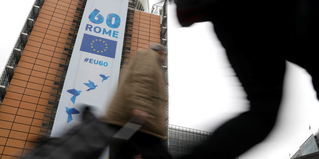 People walk past the European Commission headquarters in Brussels on which is displayed a banner celebrating the 60 years after the signing of the Treaty of Rome, in Brussels, Belgium March 20, 2017.  REUTERS/Yves Herman
