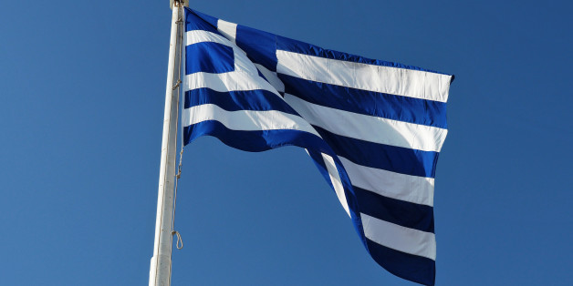 The blue and white official flag of Greece against blue sky.
