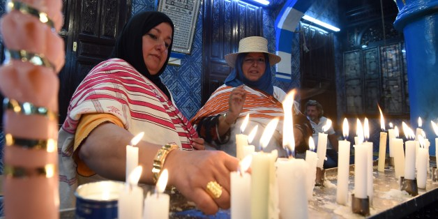 Jewish pilgrims light candles in the Ghriba synagogue on the Mediterranean resort island of Djerba on May 18, 2014. Pilgrims arrived at Tunisia's Ghriba synagogue, the oldest in Africa, expressing hope that this year would mark a turning point for the ritual despite a rise in Islamist unrest since the 2011 revolution. AFP PHOTO / FETHI BELAID        (Photo credit should read FETHI BELAID/AFP/Getty Images)