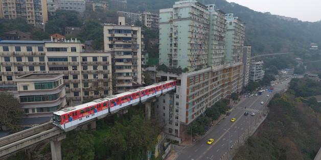 Eine Stadtbahn in der chinesischen Chingqing fährt direkt durch ein Wohnhaus
