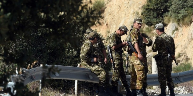 Algerian troops rest as they conduct a search operation on October 10, 2014, near the village of Ait Ouabane, 80 kilometres south of Tizi Ouza, for the body of 55-year old French tourist and moutain-guide Herve Gourdel, who was kidnapped on September 21 while hiking in Algeria's Djurdjura National Park, and beheaded three days later by a group linked to Islamic State jihadists in Iraq and Syria. Algeria is continuing to devote significant resources in Kabylia to find the body of Gourdel Herve an