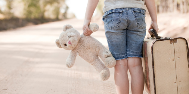 'Color photo of a sad, lonely 6-7 year old girl carrying an old, raggedy teddy bear and an old suitcase while standing on a dirt road outside.'